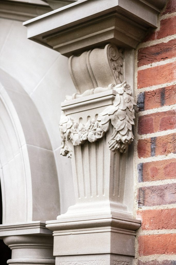 Stone carved scroll corbel with floral swag