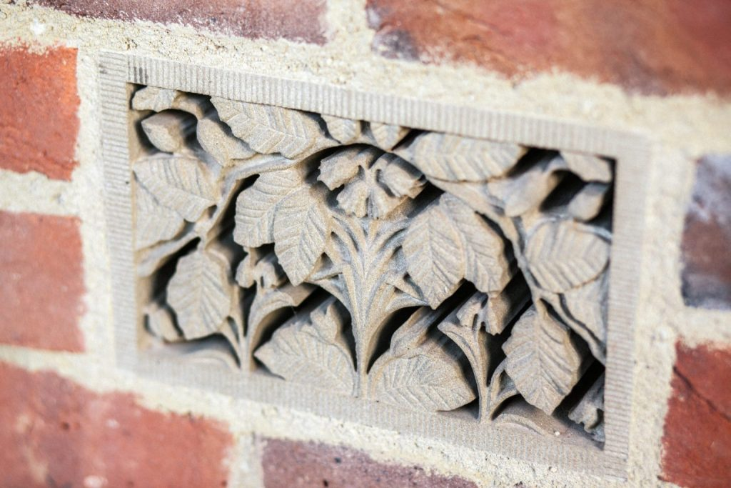 Decorative stone air brick with beech leaves and bluebells