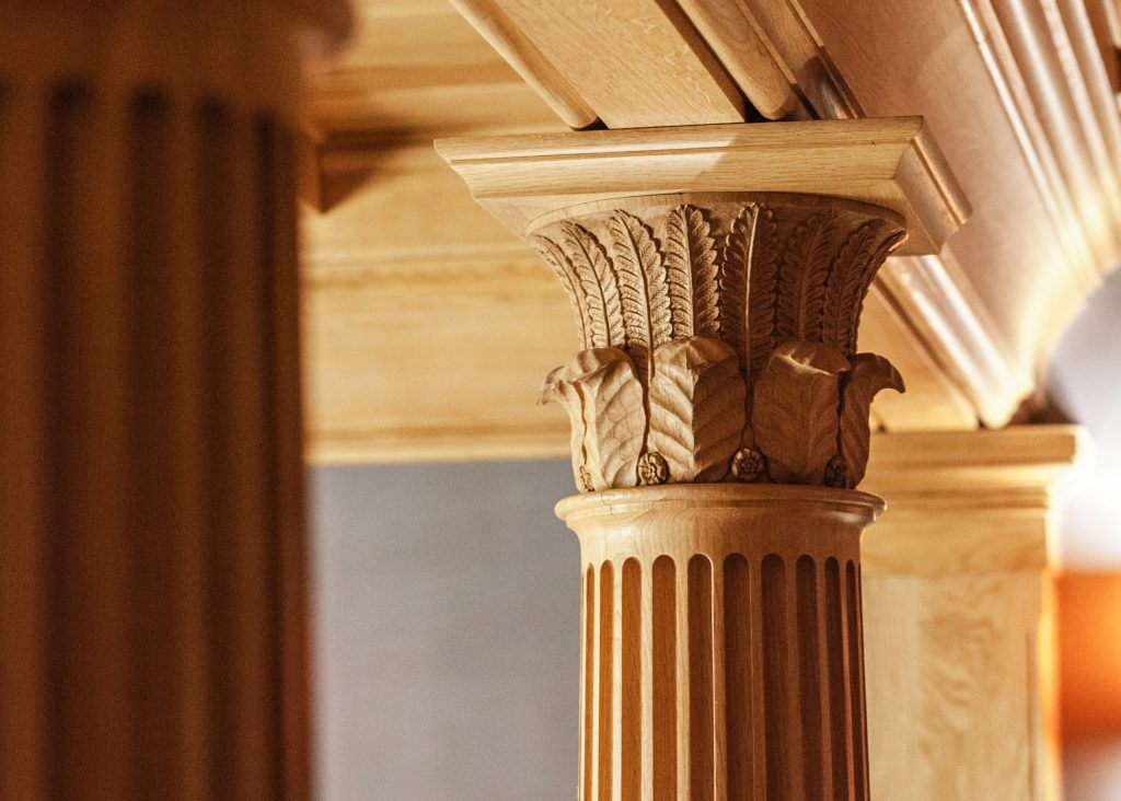 Carved wood column capital with leaves and flowers