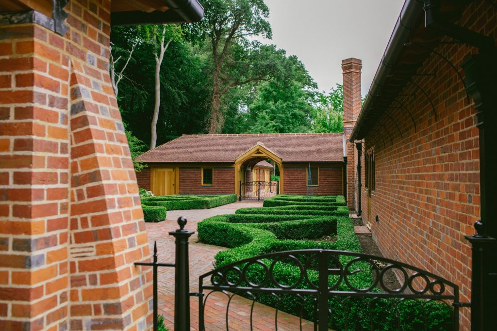 Formal kitchen garden design with bespoke metal gates and stables building in brick and oak