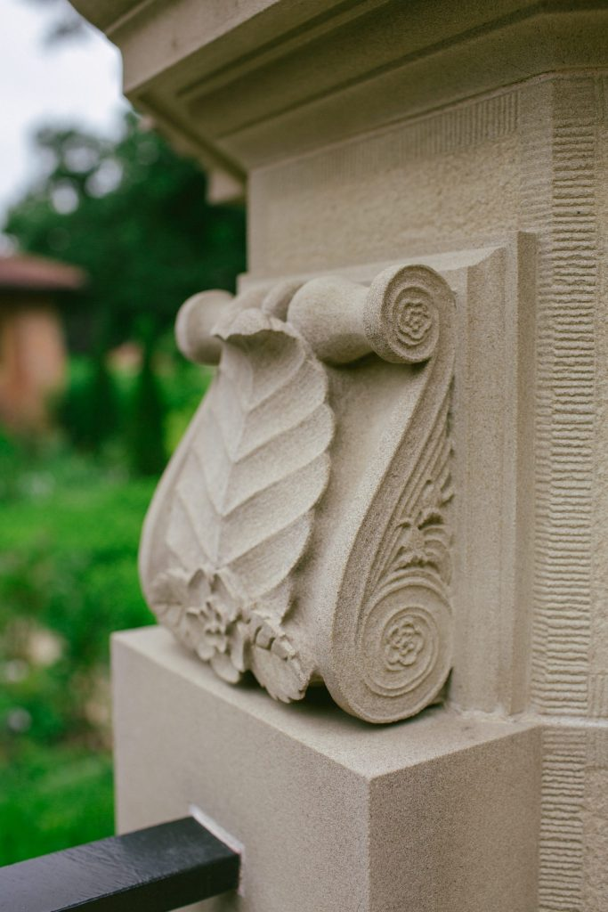 Carved stone scroll with beech leaf and dog roses
