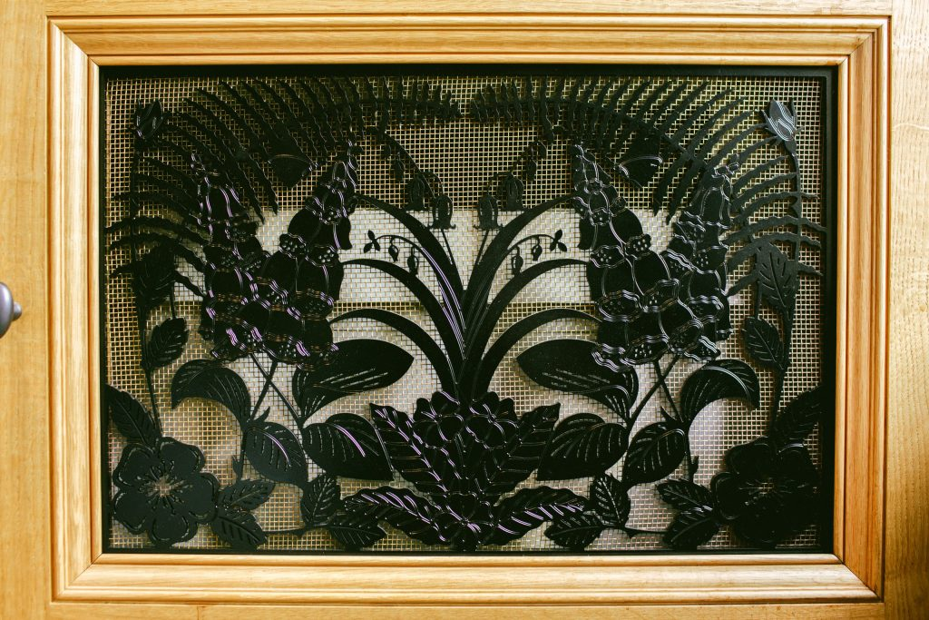Decorative metal vent cover with foxgloves, bluebells and ferns