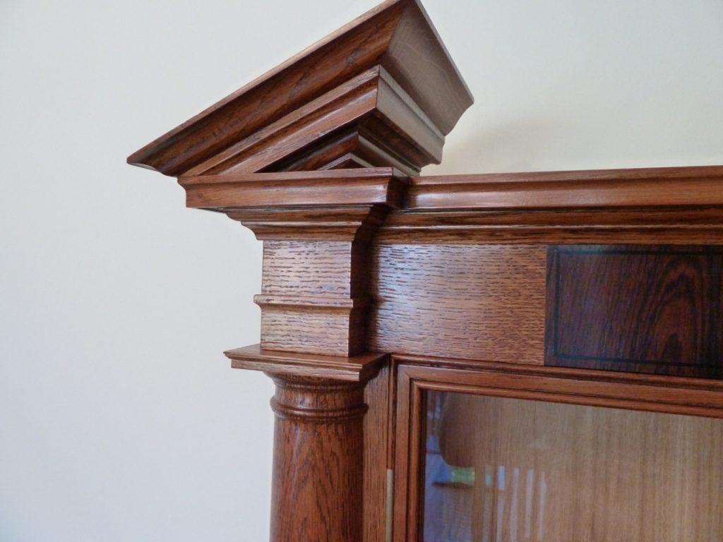 Broken pediment in Oak on classical war medal display cabinet