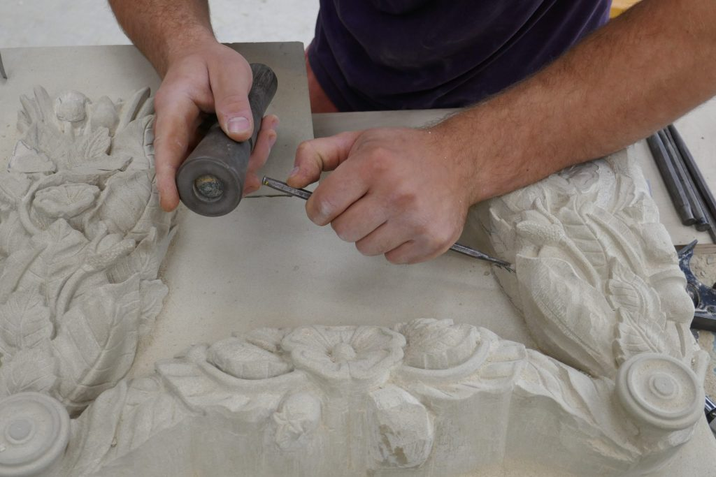 Stone mason carving intricate flowers