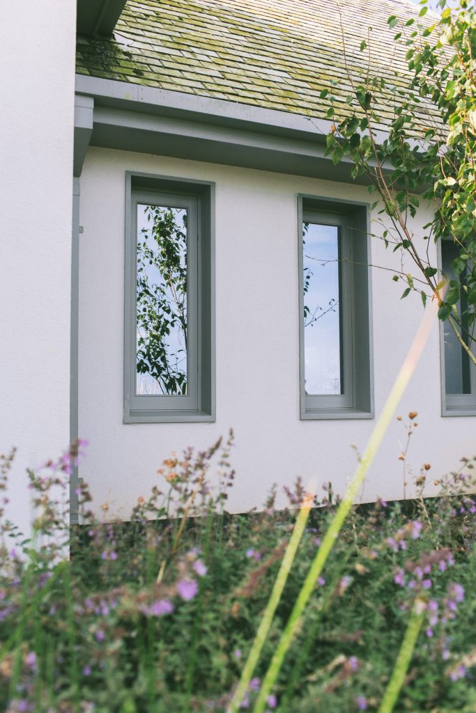 Recessed grey timber windows on traditional new home