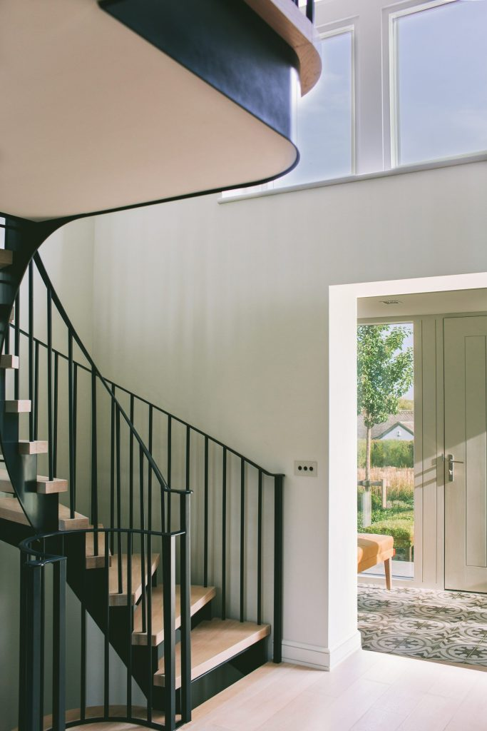 Double height light hallway with metal curved staircase