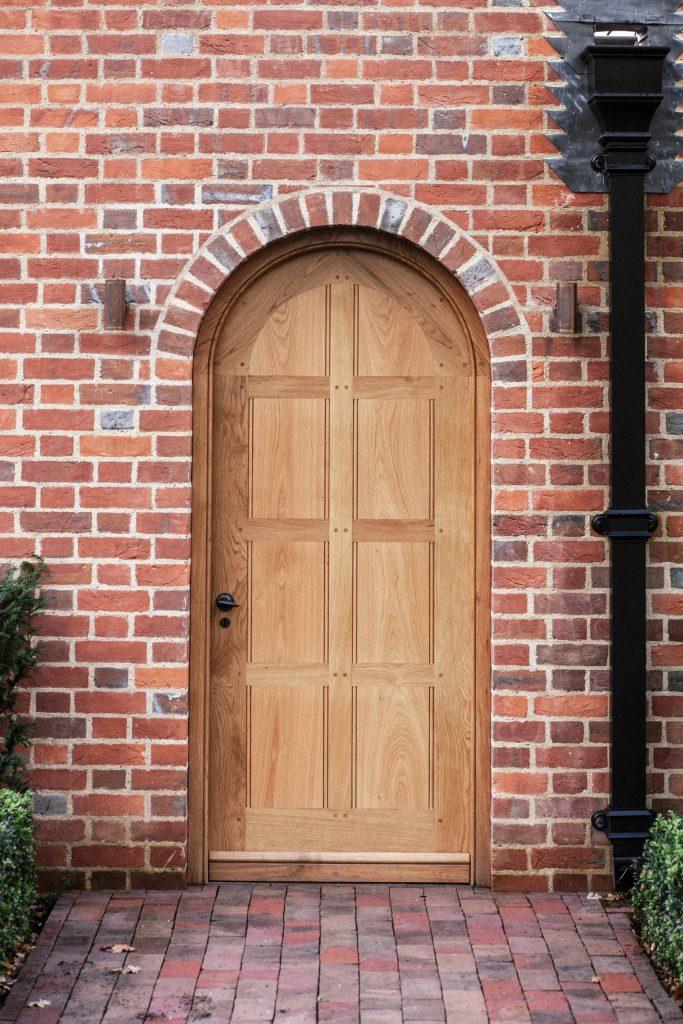 Oak panelled traditional door in brick arch