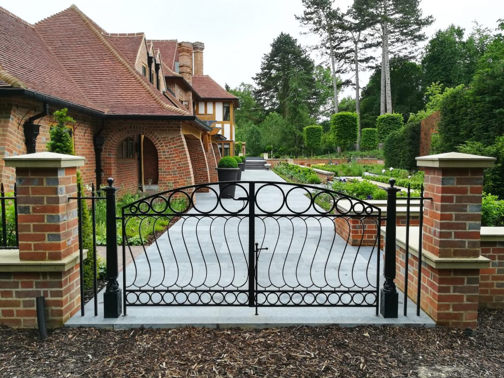 Metal Arts and Crafts gate in country house garden