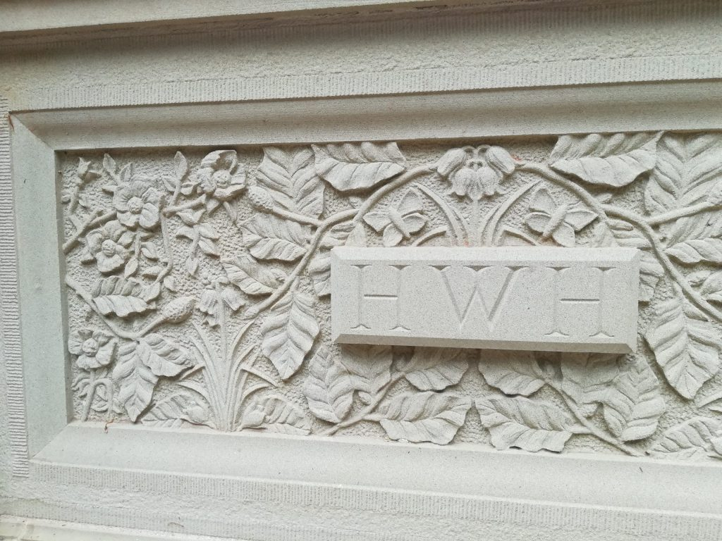 Stone carved plaque with leaves, flowers and butterflies