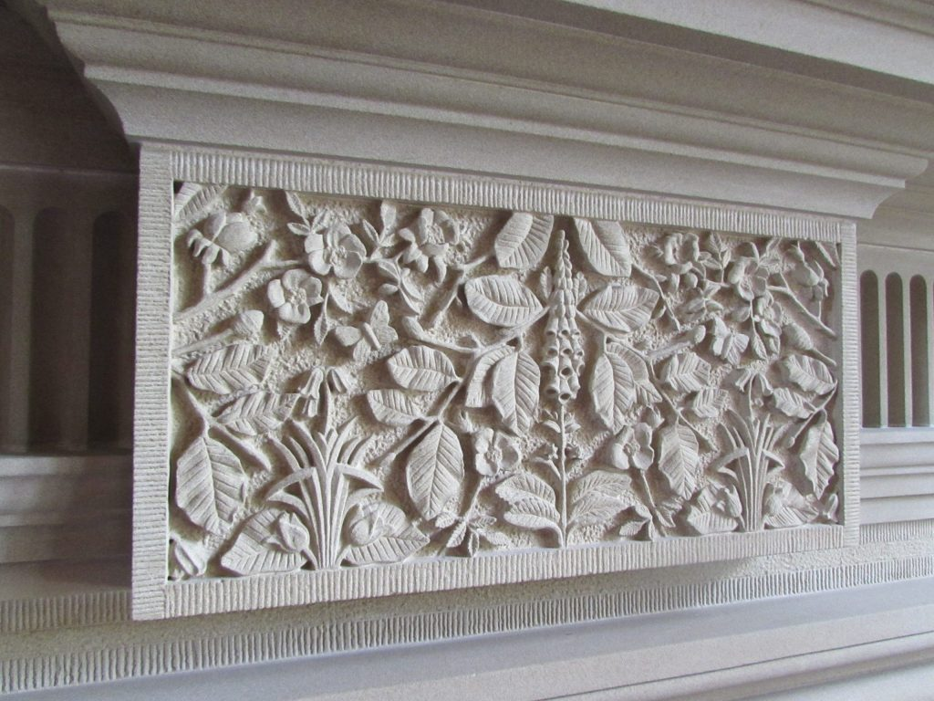 Carved stone fireplace keystone with foxgloves and beech leaves