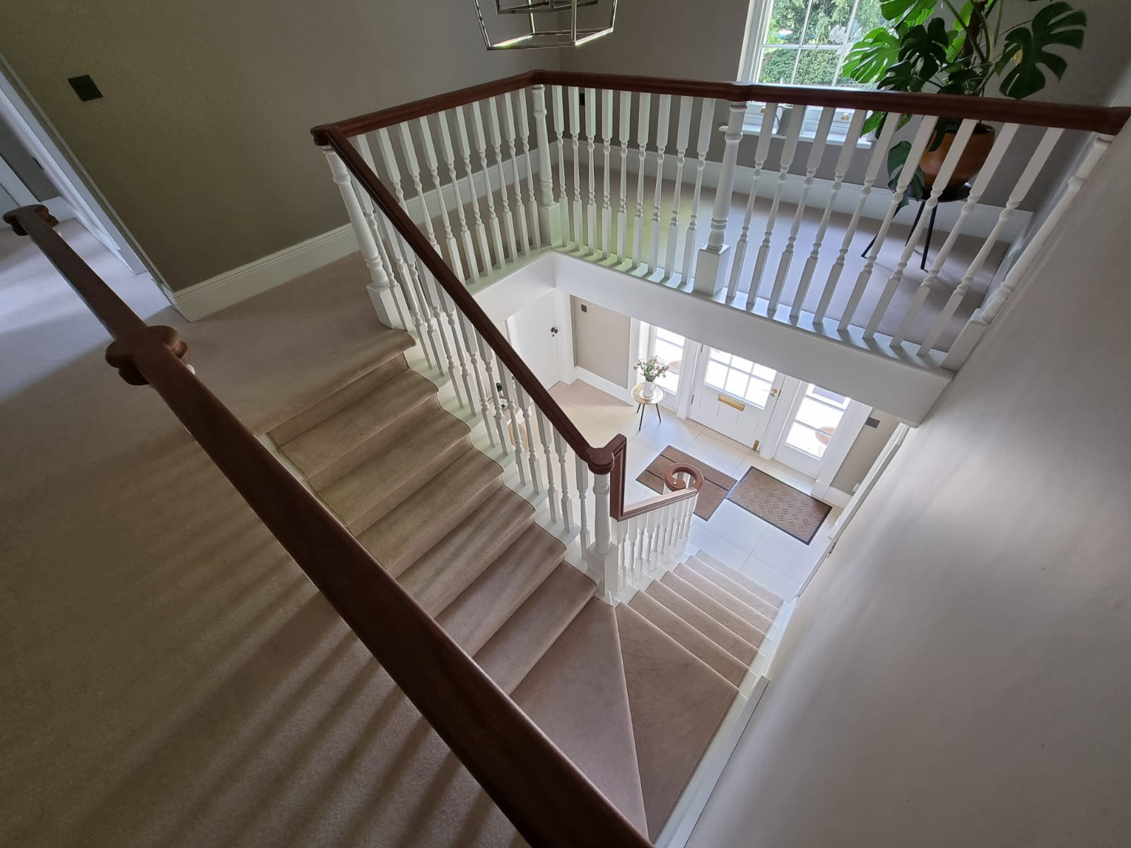 Traditional painted white staircase with wood handrail